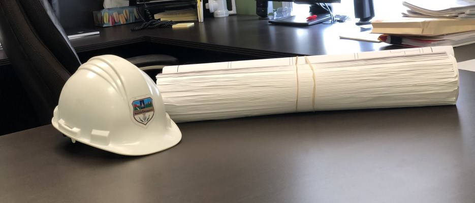 white construction hat and rolled up drawings on a desk