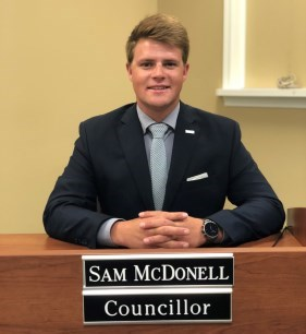Councillor Sam McDonell sitting at Council desk